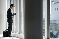 Side view of businessman using smart phone while standing by window in office 11100061925| 写真素材・ストックフォト・画像・イラスト素材|アマナイメージズ