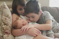 Siblings looking at baby boy while sitting on sofa 11100061958| 写真素材・ストックフォト・画像・イラスト素材|アマナイメージズ