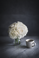 White roses in vase by coffee cup on table 11100062119| 写真素材・ストックフォト・画像・イラスト素材|アマナイメージズ