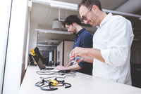 Technician examining drone while coworker using laptop computer in office 11100062150  写真素材・ストックフォト・画像・イラスト素材 アマナイメージズ
