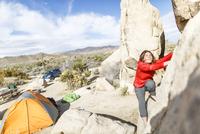 Female hiker climbing rocks at Joshua Tree National Park during sunny day 11100062191| 写真素材・ストックフォト・画像・イラスト素材|アマナイメージズ
