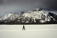 Side view of woman walking on snow covered landscape against cloudy sky 11100062269| 写真素材・ストックフォト・画像・イラスト素材|アマナイメージズ