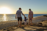 Rear view of parents holding son's hands while walking at beach during sunset