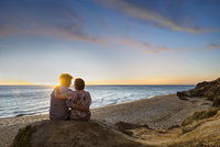 Rear view of couple sitting on rock at beach against sky during sunset