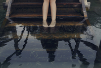 Low section of woman taking fish pedicure while standing on steps in lake 11100062328| 写真素材・ストックフォト・画像・イラスト素材|アマナイメージズ