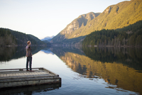 Man looking at mountains while standing on jetty over Buntzen Lake