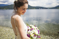 Side view of smiling bride with bouquet standing at lakeshore 11100062415| 写真素材・ストックフォト・画像・イラスト素材|アマナイメージズ