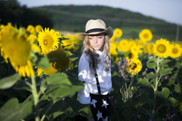 Thoughtful teenage girl in cowboy hat standing on sunflower field during sunny day 11100062434| 写真素材・ストックフォト・画像・イラスト素材|アマナイメージズ
