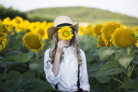 Cowgirl hiding face with sunflower while standing on field 11100062437| 写真素材・ストックフォト・画像・イラスト素材|アマナイメージズ