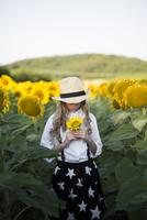 Cowgirl holding sunflower while standing on field 11100062438| 写真素材・ストックフォト・画像・イラスト素材|アマナイメージズ
