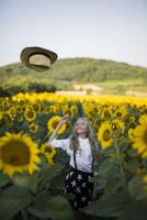 Happy teenage girl throwing cowboy hat on sunflower field 11100062442| 写真素材・ストックフォト・画像・イラスト素材|アマナイメージズ