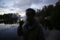 Man smoking with vape while standing on jetty against cloudy sky during sunset