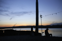 Silhouette man sitting at lakeshore against sky during sunset