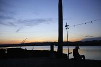 Silhouette man sitting at lakeshore against sky during sunset 11100062556| 写真素材・ストックフォト・画像・イラスト素材|アマナイメージズ