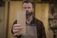 Carpenter holding wooden plank in workshop 11100062601  写真素材・ストックフォト・画像・イラスト素材 アマナイメージズ