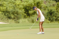 Side view of woman playing golf at golf course 11100062652| 写真素材・ストックフォト・画像・イラスト素材|アマナイメージズ