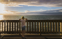 Rear view of boy looking at sea while standing by railing against cloudy sky during sunset 11100062791| 写真素材・ストックフォト・画像・イラスト素材|アマナイメージズ