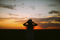 Silhouette girl wearing hat while standing against sky during sunset