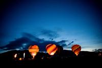 Illuminated hot air balloons on field against blue sky at dusk 11100062859| 写真素材・ストックフォト・画像・イラスト素材|アマナイメージズ