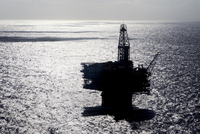 Silhouette oil platform in sea on sunny day