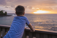 Rear view of boy looking at sea while standing by railing on pier during sunset 11100063262| 写真素材・ストックフォト・画像・イラスト素材|アマナイメージズ