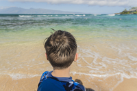 Rear view of boy standing at beach against sky during sunny day 11100063263  写真素材・ストックフォト・画像・イラスト素材 アマナイメージズ