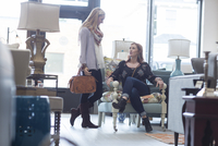 Customer looking at friend sitting on armchair in furniture store