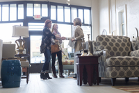 Woman looking at owner doing handshake with friend in furniture store