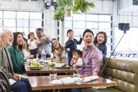 Happy family taking selfie while having dinner in restaurant 11100063411| 写真素材・ストックフォト・画像・イラスト素材|アマナイメージズ