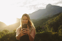 Smiling woman taking selfie while standing against mountains 11100063454| 写真素材・ストックフォト・画像・イラスト素材|アマナイメージズ