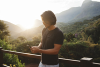 Smiling man using smart phone while standing by railing against mountains