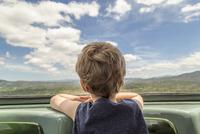 Boy looking through rear windshield while traveling in car 11100063487| 写真素材・ストックフォト・画像・イラスト素材|アマナイメージズ