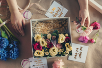 Overhead view of florist arranging flowers in box on table at flower shop 11100063530| 写真素材・ストックフォト・画像・イラスト素材|アマナイメージズ