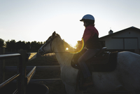 Side view of girl riding horse against clear sky at barn during sunset