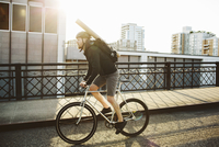 Full length of male commuter with backpack riding bicycle on bridge against sky 11100063579| 写真素材・ストックフォト・画像・イラスト素材|アマナイメージズ