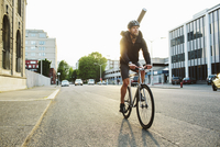 Male commuter riding bicycle on road against clear sky in city 11100063580| 写真素材・ストックフォト・画像・イラスト素材|アマナイメージズ