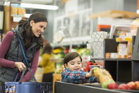 Mother and son keeping food on checkout counter at supermarket