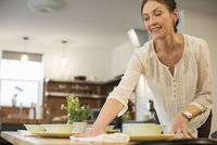 Woman arranging table at home 11100063707| 写真素材・ストックフォト・画像・イラスト素材|アマナイメージズ