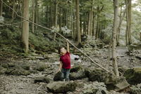 Playful boy lifting stick while standing in forest