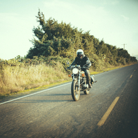 Male biker riding motorcycle on country road against sky 11100064065| 写真素材・ストックフォト・画像・イラスト素材|アマナイメージズ