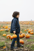 Side view of boy carrying pumpkin while walking at farm against sky during winter 11100064094| 写真素材・ストックフォト・画像・イラスト素材|アマナイメージズ
