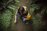 High angle view of mother and son crouching on field at park 11100064125| 写真素材・ストックフォト・画像・イラスト素材|アマナイメージズ