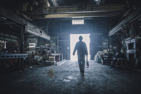 Rear view of worker carrying adjustable wrench while walking in factory 11100064141| 写真素材・ストックフォト・画像・イラスト素材|アマナイメージズ