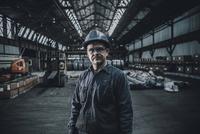 Portrait of confident male worker standing in steel industry 11100064164| 写真素材・ストックフォト・画像・イラスト素材|アマナイメージズ