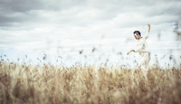 Man with arms outstretched dancing on field against cloudy sky at farm 11100064175| 写真素材・ストックフォト・画像・イラスト素材|アマナイメージズ