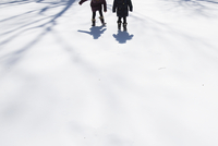 Low section of sisters walking on snow covered field
