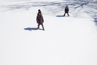 High angle view of sisters walking on snow covered field