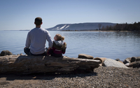 Rear view of father and daughter sitting on log at lakeshore against clear sky during sunny day 11100064325| 写真素材・ストックフォト・画像・イラスト素材|アマナイメージズ