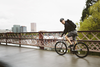 Side view of male commuter riding bicycle on bridge over river against sky 11100064372| 写真素材・ストックフォト・画像・イラスト素材|アマナイメージズ