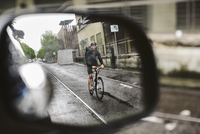 Male commuter riding bicycle on wet street seen through side-view mirror of car 11100064378| 写真素材・ストックフォト・画像・イラスト素材|アマナイメージズ